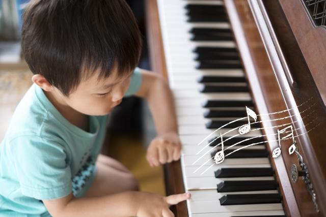 子供がピアノで遊び弾きしている